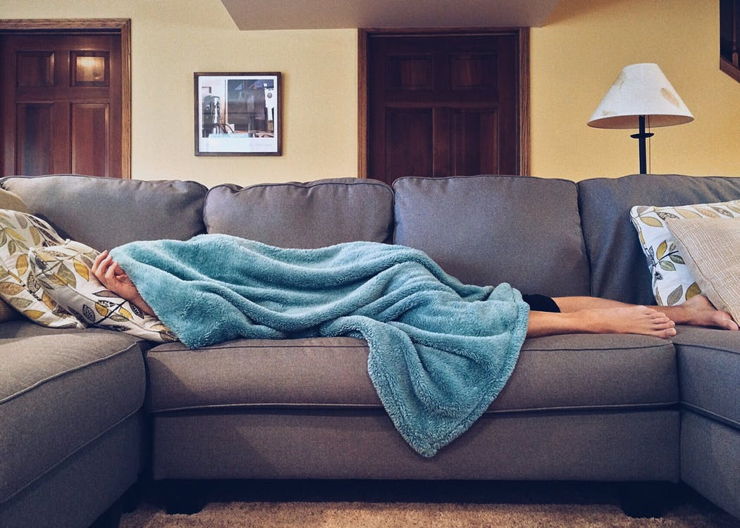 Man with blanket over him, laying on couch